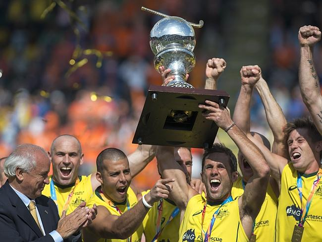Australian players celebrate holding the trophy after winning the hockey World Cup as Leandro Negre, the President of the International Hockey Federation FIH, looks on.