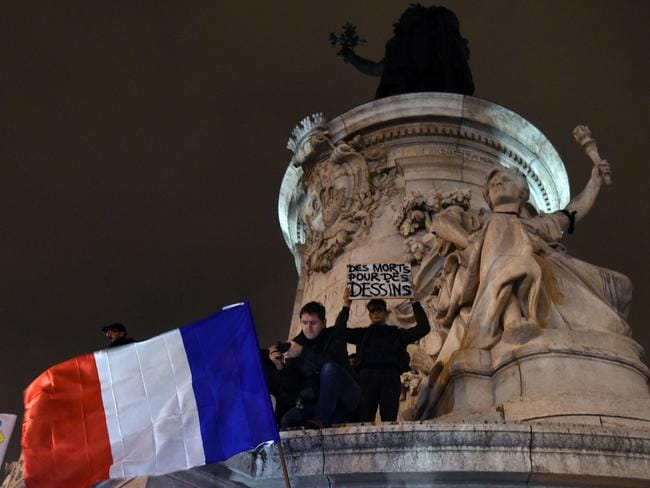 Liberty ... a black armband was placed on Lady Liberty at Place de la Republique as demonstrators for peace wave the French flag. Picture: AFP/Dominique Faget