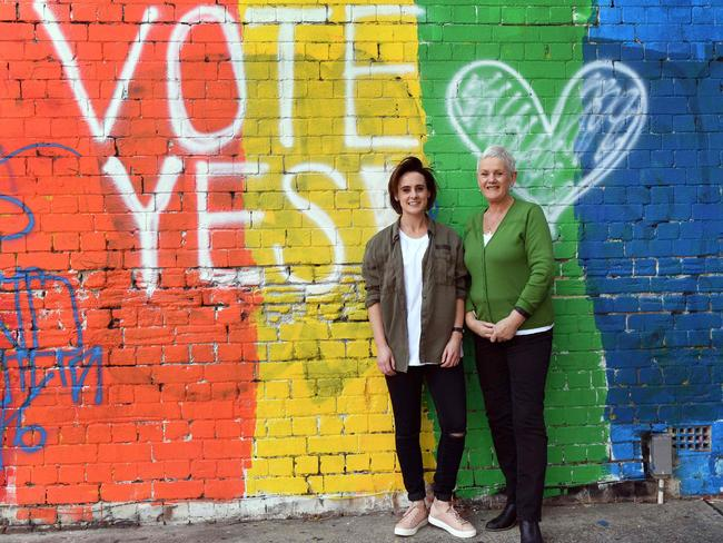 People pose for a photo in front of a Vote Yes mural supporting same-sex marriage in Sydney on September 7, 2017. Australia's High Court on September 7, threw out two challenges to a same-sex marriage postal vote planned by the government, paving the way for a national survey on whether such unions should be legalised. / AFP PHOTO / WILLIAM WEST