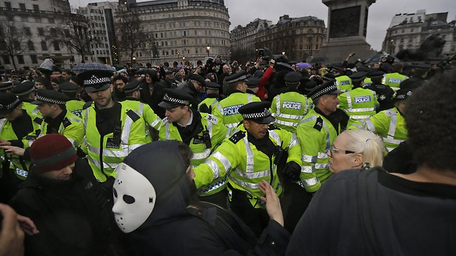 British police officers scuffle with people gathered in central London's Trafalgar square, Saturday, April 13, 2013, with a party to mark the death of former British Prime Minister Margaret Thatcher. (AP Photo/Lefteris Pitarakis)