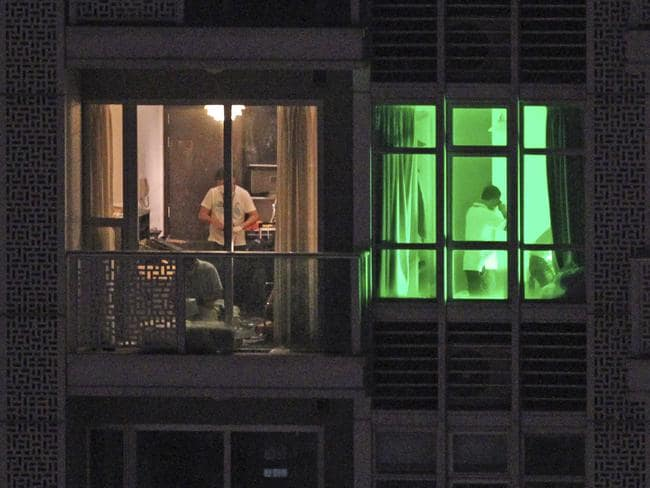 Police investigate the apartment of a man in Hong Kong's Wan Chai night-life and red light district. Pic:AP/Apple Daily.