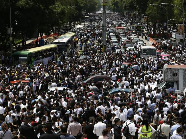 People evacuated from office buildings gather in Reforma Avenue. Picture: AP / Marco Ugarte