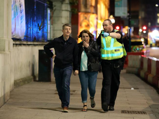 A police officer escorts members of the public to safety at London Bridge. Picture: Getty