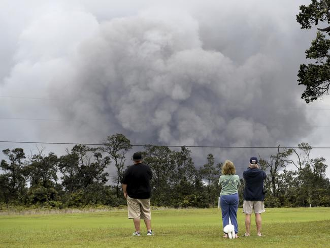 People watch as ash rises from the summit crater of Kilauea volcano. Picture: AP Photo/Caleb Jones