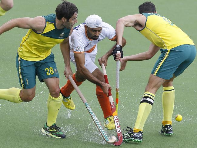 Australia's Kiel Brown, left, Mark Knowles, right, tackle India's Gurwinder Chandi.