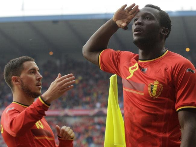 Eden Hazard practices for his upcoming performance at the opera, while Romelu Lukaku salutes.