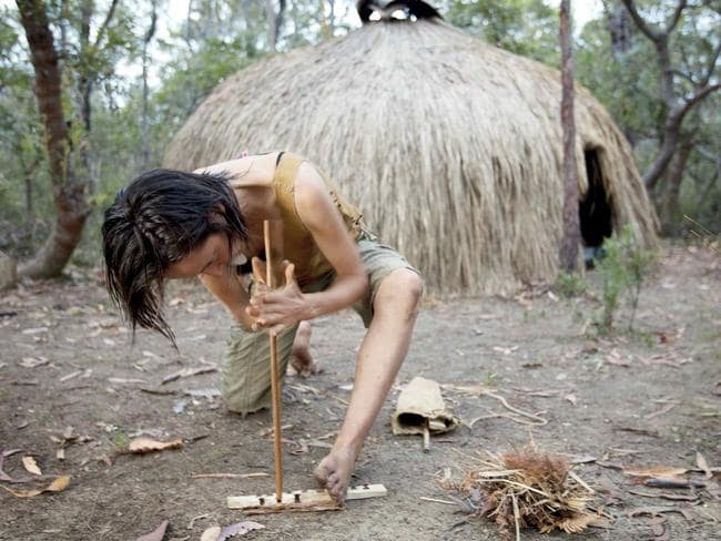 Claire trying to light a fire with no matches. She's using a Grasstree stalk and no small measure of elbow grease to coax a coal from the wood shavings in the notch in her Wild Tobacco baseboard. Picture: Australian Geographic