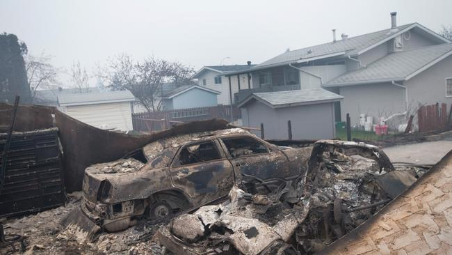 The remains of c-harred vehicles sit in a neighborhood heavily damaged by a wildfire in Fort McMurray, Alberta, Canada.