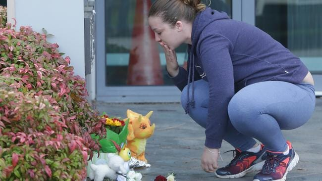 Flowers and toys are left at the scene in a car park where the 4-year-old was killed. Picture: Hamish Blair