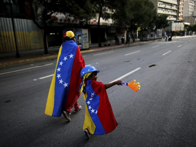 An anti-government demonstrator and her daughter wrapped in the Venezuelan flag walk on an empty street in Caracas. Picture: AP