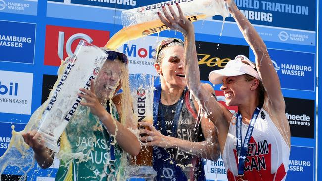 Gwen Jorgensen of the United States, Emma Jackson of Australia and Kirsten Sweetland of Canada celebrate at the podium after the Women's ITU World Triathlon sprint event.
