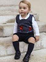 The 17-month-old Prince George sits in a courtyard at Kensington Palace, where his parents, Prince William and Kate, have a London apartment. Picture: AFP