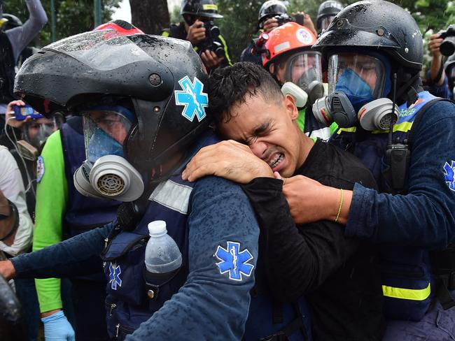 A wounded anti-government activist is carried away by medics during clashes with the police in Caracas. Picture: AFP