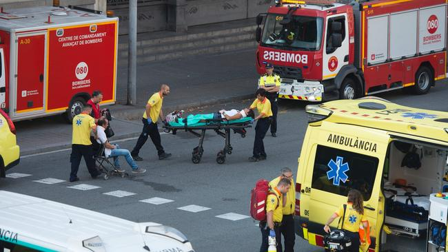A victim is stretchered towards emergency vehicles parked outfront of the Estacio de Franca (Franca station) in central Barcelona. Picture: AFP / Josep Lago.
