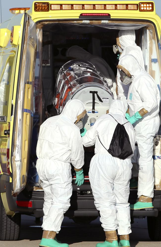in isolation ... aid workers and doctors transfer Miguel Pajares, a Spanish priest who was infected with the Ebola virus while working in Liberia, from a plane to an ambulance. Picture: AP/Spanish Defense Ministry