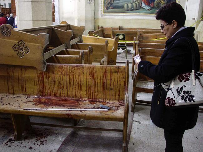 An Egyptian woman uses her cell phone to take pictures of the destruction, debris, and bloodstains inside the Mar Girgis Coptic Orthodox Church in Tanta. Picture: AFP