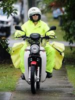 A local postman endures the wet weather on his motorbike during a rainy afternoon in Wilston. Pic: Tara Croser