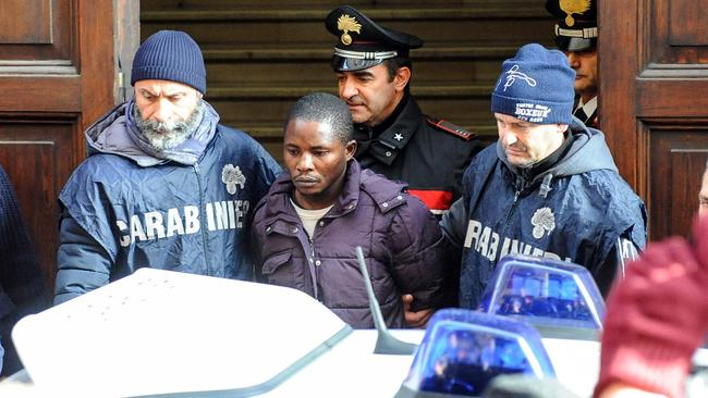 A man identified as Desmond Lucky is escorted by two police officers after being arrested in connection with the probe for the gruesome killing of a young Italian woman, 18-year-old Pamela Mastropietro, whose dismembered remains were found in two suitcases. Picture: Fabio Falcioni/ANSA via AP