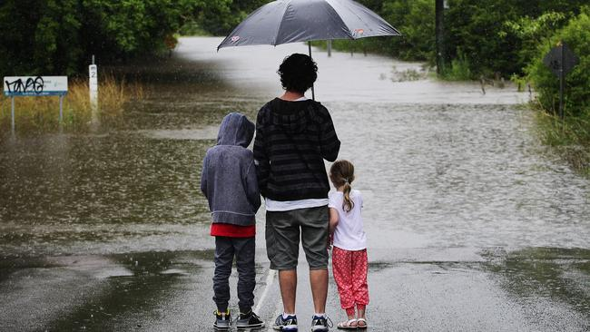 Local resident Shane Hawkins and his kids Jasper and Lilah check out the severe flooding on Burns Road in Ourimbah.