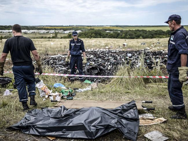 Grim task ... Ukrainian State Emergency Service employees collect bodies of victims at the site of the crash of a Malaysia Airlines plane in Grabove, in rebel-held east Ukraine. Picture: Bulent Kilic