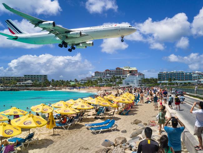 A commercial airline landing at the Princess Juliana International Airport in St Maarten. The airport is a hotspot for tourists with many bars displaying arrival times.