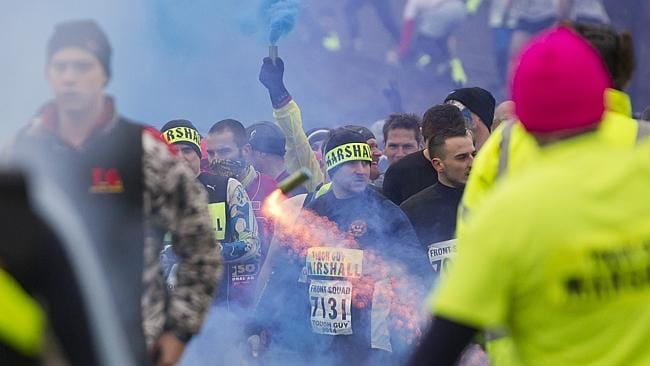 Fireworks and smoke bombs are thrown as competitors wait to start.