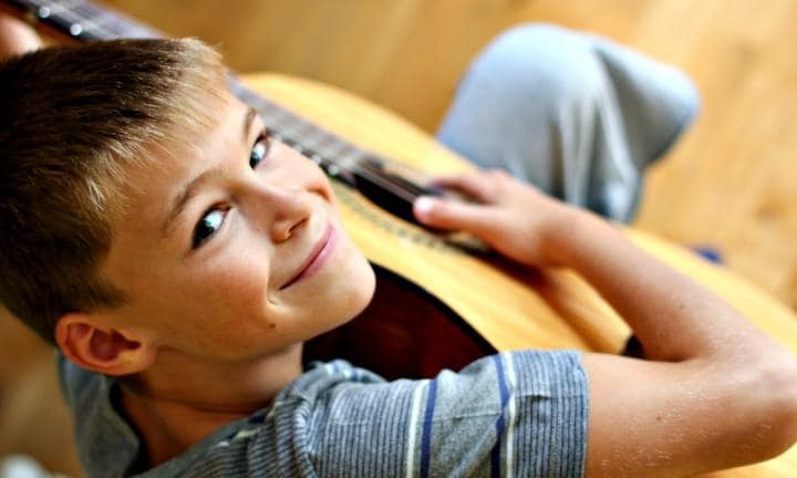 portrait of a little smiling boy with guitar