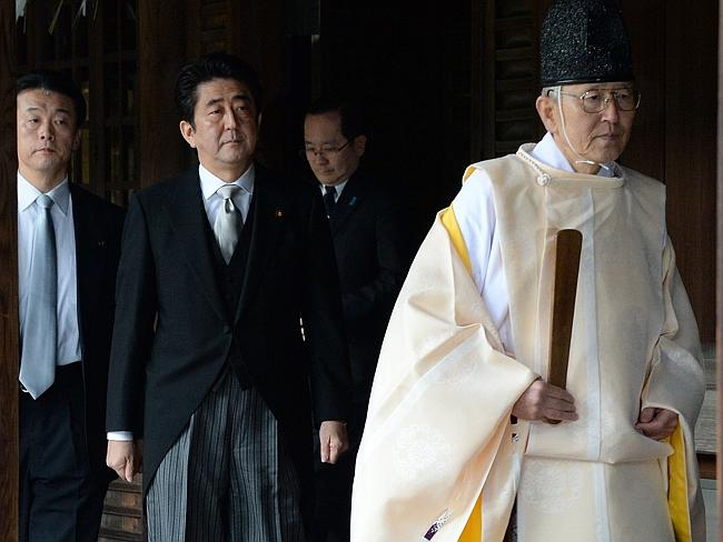 Honouring criminals ... a Shinto priest leads Japanese Prime Minister Shinzo Abe, centre, as he visits the controversial Yasukuni war shrine in Tokyo. US Vice President Joe Biden spent an hour trying to persuade Japan's prime minister not to visit the controversial two weeks before the pilgrimage that sparked fury in Asia. Picture: AFP / Toru Yamanaka