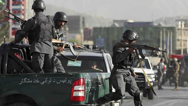 Afghan security personnel arrive after a deadly suicide attack outside a cricket stadium.