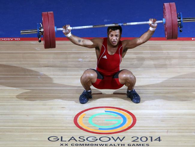 Papua New Guinea's Toua Udia competes in the snatch of the men's 77kg.