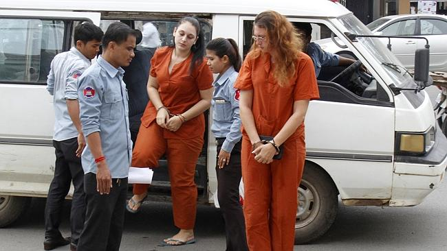 Convicted ... Australian Ann Yoshe Taylor, right, and French teen Charlene Savarino, centre, get off a van in front of the Phnom Penh Municipal Court in Phnom Penh, Cambodia. Picture: Khem Sovannara