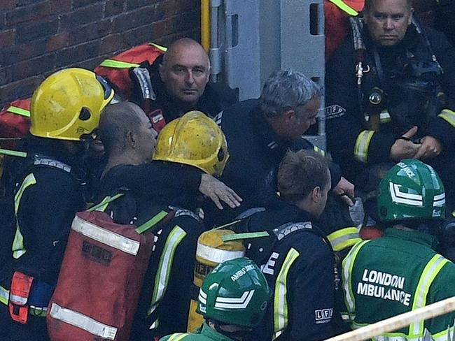 A man is rescued from the Grenfell Tower by firefighters. Picture: Leon Neal/Getty Images