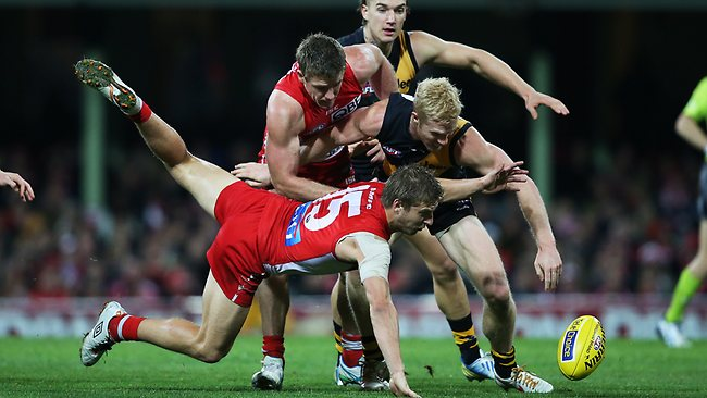 Sydney's Kieren Jack attacks the ball ahead of Richmond's Steven Morris during AFL match between Sydney Swans v Richmond Tigers at the SCG. Picture: Hillyard Philip