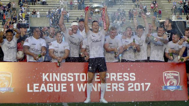 Toronto Wolfpack captain Craig Hall hoists the trophy as the first-year rugby league team celebrates winning the Kingstone Press League 1 title and promotion to the English Championship.