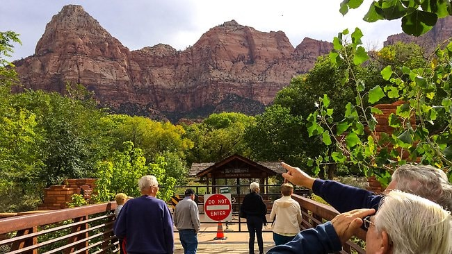 Tourists point out landmarks visible from the closed gate to Zion National Park in Utah. Picture: AP