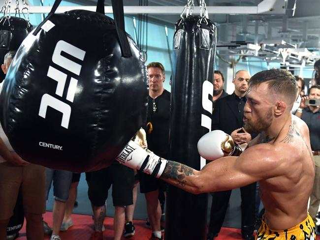 UFC lightweight champion Conor McGregor hits an uppercut bag during a media workout.