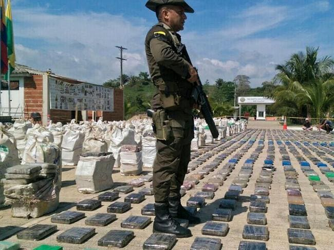 A Colombian police officer stands guard over the seized cocaine. Picture: AFP/ Policia Nacional handout
