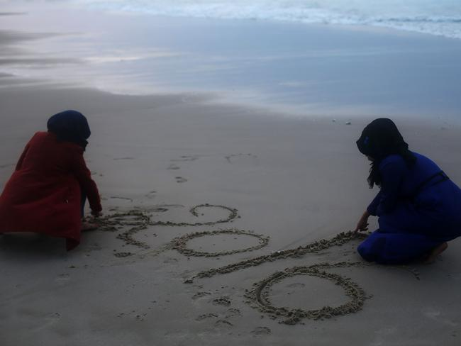Palestinian women play in the sand on the last day of the year.