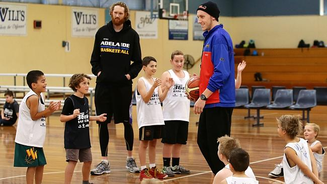 Adelaide 36ers Luke Schenscher, left, and Mitch Creek during a coaching clinic with child