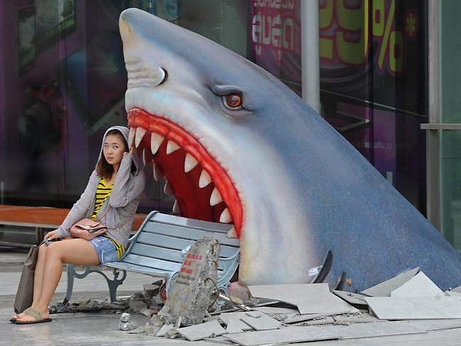 """Photos of the Year 2012: A foreign tourist sits next to a large art display of a shark displayed at a shopping mall in Bangkok on July. Thailand is a tourist magnet but its image as the """"Land of Smiles"""" has been tested in recent years by deadly political unrest, devastating floods and a bungled bomb plot involving Iranian suspects. Photo: AFP/Pornchai Kittiwongsakul"""