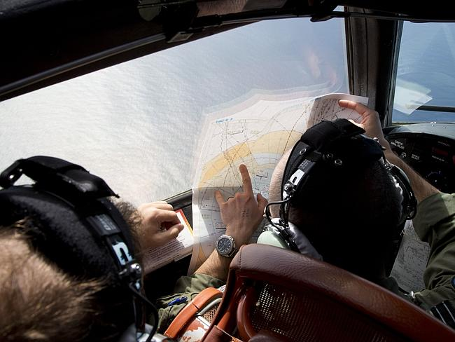 Search...Flight Lt. Jayson Nichols looks at a map onboard a RAAF search operation over the Indian Ocean. Picture: AP