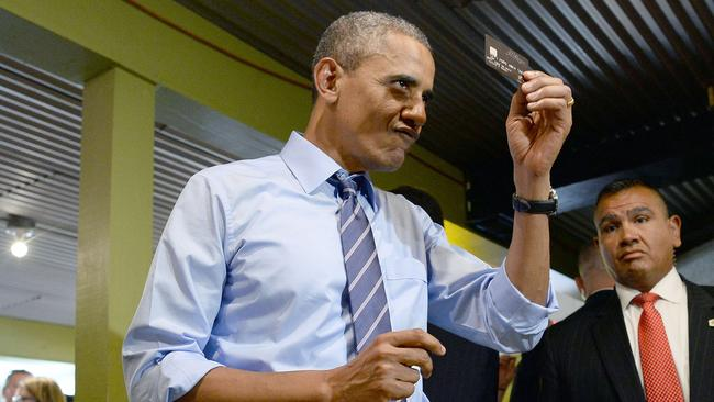 US President Barack Obama holds up his credit card as he pays for his order at BBQ restaurant in Austin, Texas. AFP/Jewel Samad