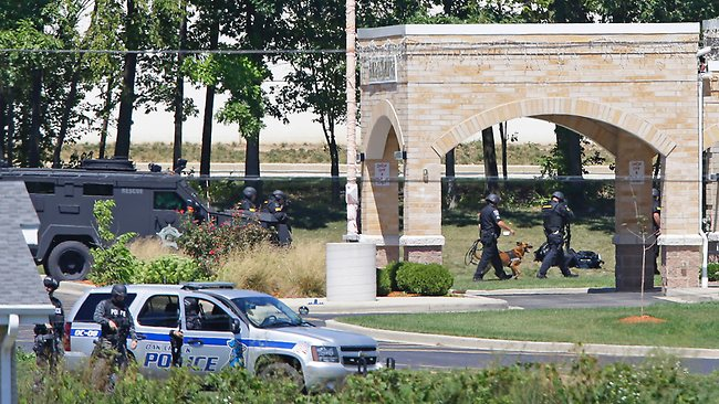 Police approach the Sikh Temple of Wisconsin in Oak Creek where a shooting took place. (AP Photo/Jeffrey Phelps)