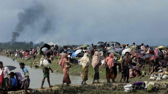 Smoke billows from a burning village as thousands of Rohingya flee their homes. Picture: K.M. Asad