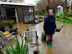 Kath Arbon watches the creek take over her backyard and start to flow into her house at Hahndorf. Picture: Mark Brake