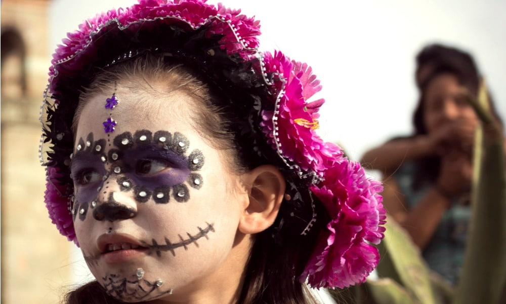 "Outside the Church of Santo Domingo de Guzmán in Oaxaca, Mexico, a girl is dressed up for Day of the Dead celebrations (""Día de los Muertos"" in Spanish)."