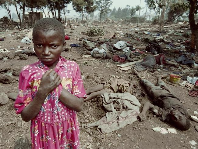 A Rwandan refugee stands on July 17, 1994 among the corpses of over 100 of her compatriot