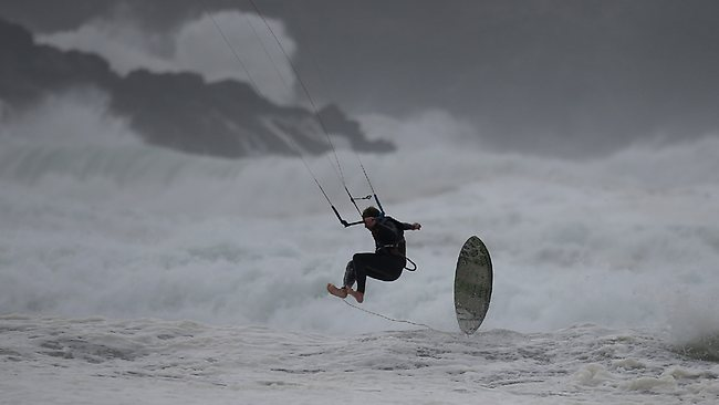 A kite surfer enjoys the stormy seas at Fistral Beach in Newquay, Cornwall. Millions of people in parts of the UK have been told to brace themselves for what is predicted to be one of the worst storms for years, with heavy rain and hurricane-force winds expected tonight and tomorrow morning as the storm hits the South West.