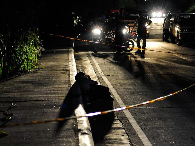 An alleged drug dealer, his hands bound and his head wrapped in tape, lies in the foreground after being shot dead in a Manila street. Picture: Getty Images