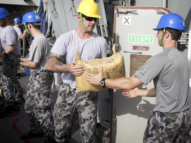 Confiscated drugs ... Petty Officer Boatswain Ewen Jenkins (second right) assists with the loading of the seized hashish on-board HMAS Darwin.